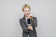Portrait of smiling blond woman showing her smartphone in front of grey background - TCF004242