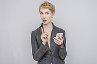 Portrait of blond woman with wagging finger and smartphone in front of grey background - TCF004249