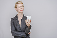Blond woman looking at her smartphone in front of grey background - TCF004250