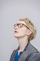Blond woman with closed eyes in front of grey background - TCF004268