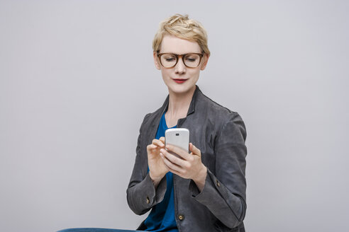 Portrait of smiling blond woman using smartphone in front of grey background - TCF004271