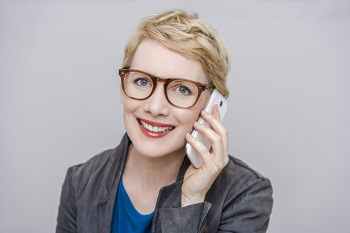 Portrait of smiling blond woman wearing glasses telephoning with smartphone in front of grey background - TCF004279
