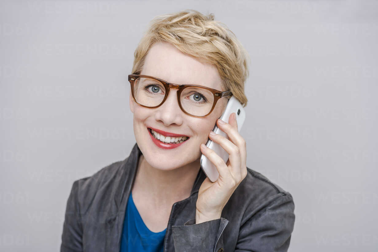 Portrait of smiling blond woman wearing glasses telephoning with smartphone in front of grey background - TCF004279 - Tom Chance/Westend61