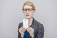 Blond woman taking a selfie with her smartphone - TCF004282