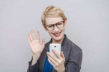 Smiling blond woman taking a selfie with her smartphone - TCF004284