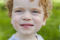 Portrait of smiling little boy covered with ice cream - TCF004253