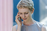 Portrait of smiling blond woman telephoning with smartphone looking down - TCF004306