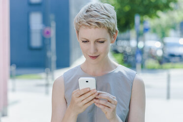 Portrait of blond woman with smartphone - TCF004308