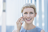 Portrait of smiling blond woman telephoning with smartphone - TCF004317