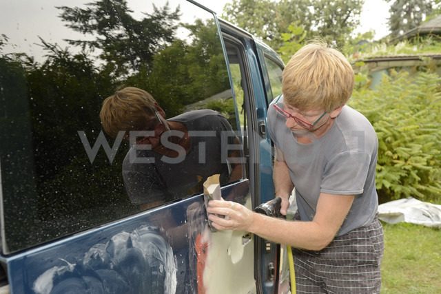Germany, Zeuthen, Man mending car paint - BFRF000502