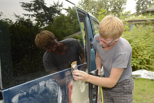 Germany, Zeuthen, Man mending car paint - BFRF000502