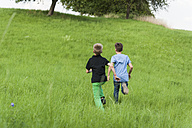Two boys running on a meadow uphill - PAF000856