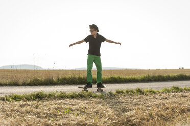 Boys standing on his skateboard in front of a stubble field - PAF000860