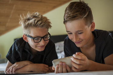 Portrait of two boys lying on bed using smartphone - PAF000864