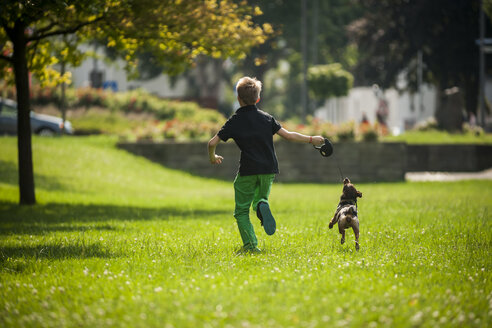 Boy running with his dog on a meadow - PAF000888
