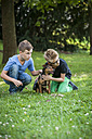 Two boys crouching on a meadow  with their dog - PAF000891