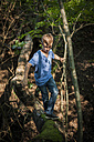 Boy balancing on a deadwood in the forest - PAF000875