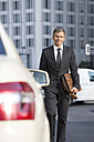 Germany, Berlin, Businessman taking a taxi - FKF000641