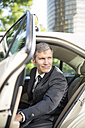 Germany, Berlin, Businessman getting out of taxi - FKF000631