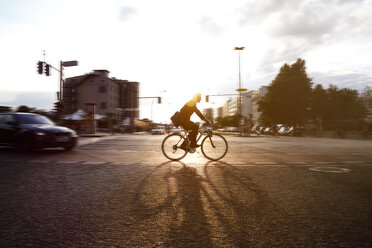 Germany, Berlin, Businessman cycling in the city - FKF000636