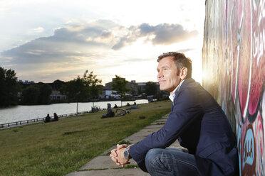 Germany, Berlin, Businessman crouching near Berlin wall, contemplating - FKF000643
