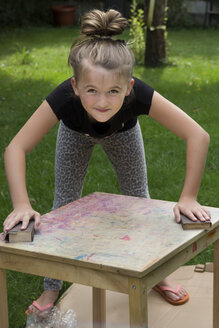 Girl standing in the garden working on a wooden table with sandpaper blocks - YFF000223