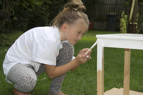 Little girl painting wooden table with white varnish - YFF000224