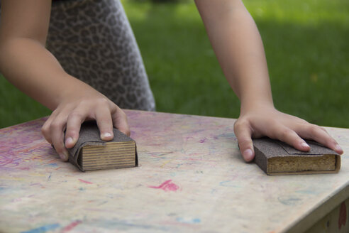 Girl's hands working on a wooden table with sandpaper blocks - YFF000227