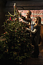 Mother and daughter decorating Christmas tree in a farmhouse - HHF004860