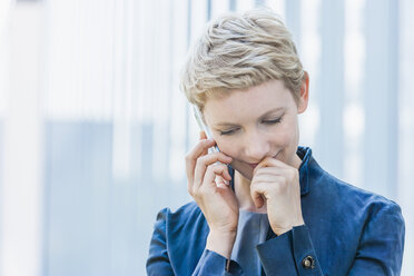 Portrait of blond woman telephoning with smartphone looking down - TCF004439