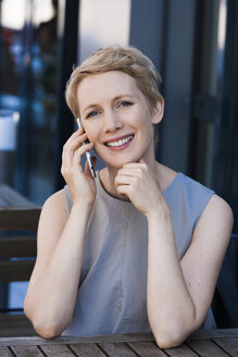 Portrait of smiling blond woman telephoning with smartphone - TCF004441