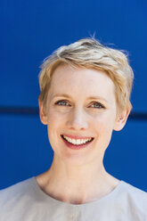 Portrait of smiling blond woman in front of blue background - TCF004452