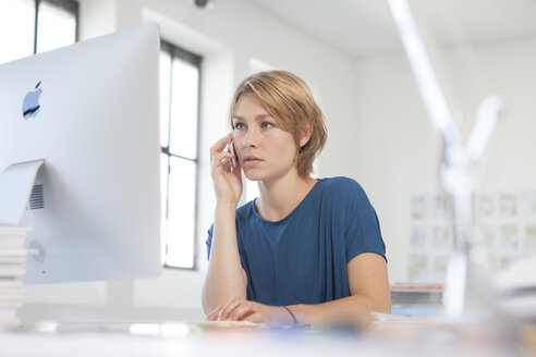 Portrait of young woman telephoning at her desk in a creative office - RBF001804