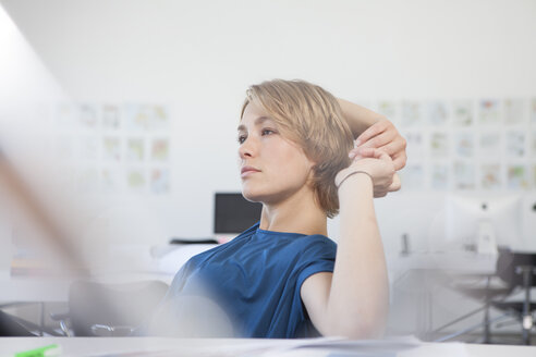 Portrait of pensive young woman at her desk in a creative office - RBF001836
