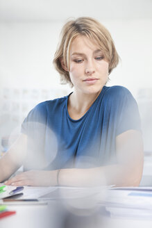 Portrait of working young woman at her desk in a creative office - RBF001841