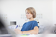 Portrait of pensive young woman at her desk in a creative office - RBF001844