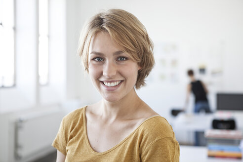 Portrait of smiling young woman in a creative office - RBF001813