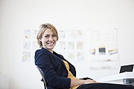 Portrait of smiling young woman at her desk in a creative office - RBF001847