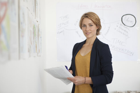 Portrait of young woman standing besides a wall with concepts in an office - RBF001850