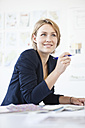 Portrait of smiling young woman at her desk in a creative office - RBF001853