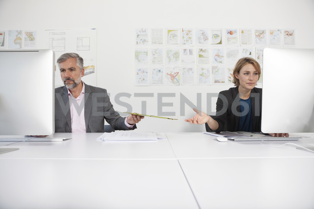 Two indifferent colleagues at their desks in an office - RBF001868