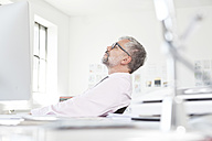 Man working relaxing at his desk in an  office - RBF001826