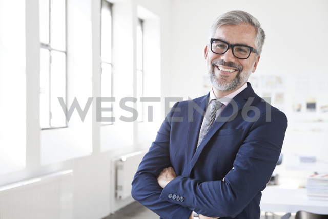 Portrait of smiling businessman with crossed arms in an office - RBF001884 - Rainer Berg/Westend61