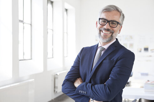 Portrait of smiling businessman with crossed arms in an office - RBF001884