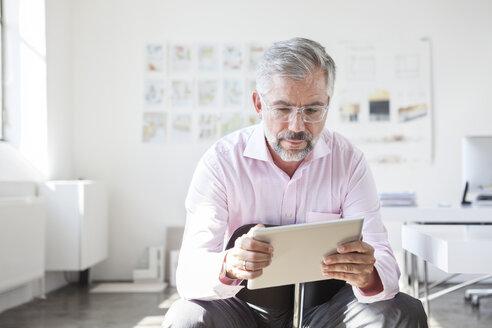 Portrait of businessman using digital tablet in an office - RBF001893