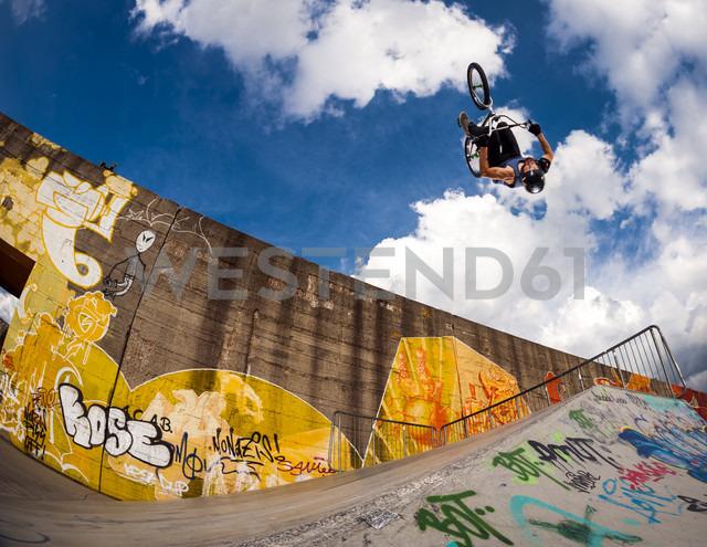Germany, Young man performing stunt on BMX bike - KJ000307
