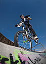 Germany, Young man performing stunt on BMX bike - KJ000310