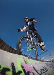 Germany, Young man performing stunt on BMX bike - KJ000310