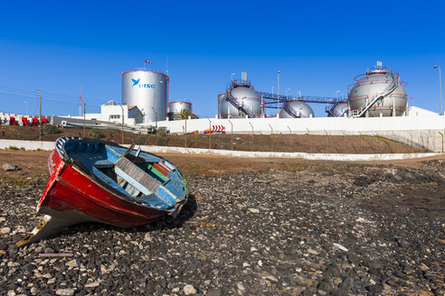 Spain, Canary Islands, Lanzarote, Arrecife, industrial plant of Disa company, wooden boat on seafront - AM002766