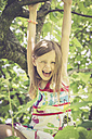 Portrait of laughing little girl climbing on a tree in the garden - SARF000784